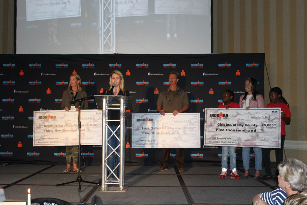 Fundraising Programs Manager, Whitney Staloch, presents our IMF Grant Beneficiaries with checks totaling over $88,000 at the IMFL Athlete Welcome Banquet!